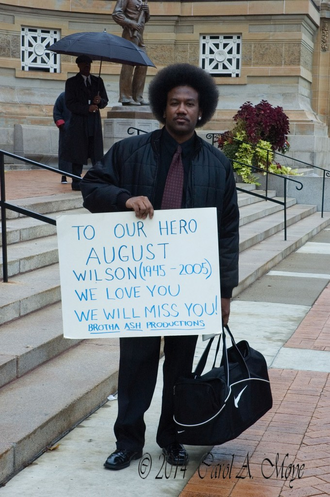 Brother Ash with a sign in memory of August Wilson